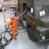 Man in orange suite removing asbestos from a vehicle