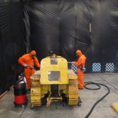 Two men in orange suites using a Vehicle Asbes Decontamination